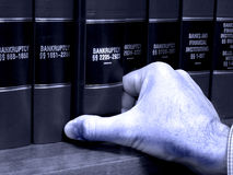 Hand on Book on Bankruptcy Stock Images