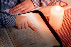Hand on book beside candle. Stock Photography