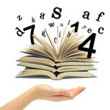 Hand and a book with departing letters, numbers royalty free stock images