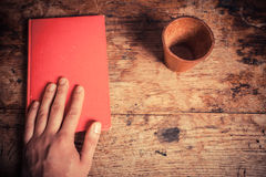 Hand, book and leather dice cup Stock Photo