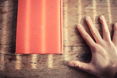 Hand and book on table Royalty Free Stock Photo