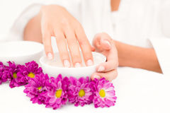 Hand in bowl along flowers and candle Royalty Free Stock Images