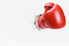 Hand in boxing glove broke through the paper wall. Place an empty paper for your text Stock Images