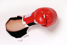 Hand in boxing glove through paper hole Royalty Free Stock Images