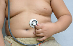 Hand boy check big stomach by stethoscope Royalty Free Stock Photography