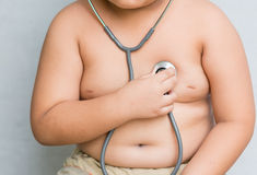 Hand boy check heart by stethoscope. Hand fat boy check heart by stethoscope Royalty Free Stock Image