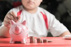 Hand boy put coin to piggy bank, saving money Royalty Free Stock Photography