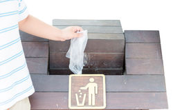 Hand boy throwing plastic bag into bin Royalty Free Stock Images