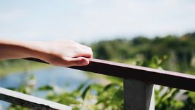 The hand of a boy walking along the waterfront. He`s holding on to the railings. Walk around town. Entertainments. Children stock footage