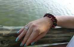 Hand with bracelet near the sea. Women hand with colorful bracelet silver ring and nails colored blue color lies on wooden border near the sea Stock Image