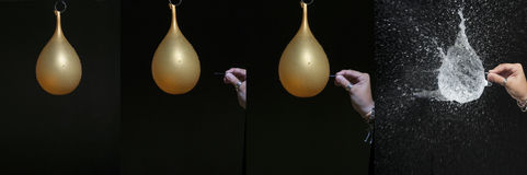 Hand breaking a balloon with a needle Stock Photography