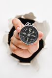 Hand breakthrough wall holding compass Royalty Free Stock Photos