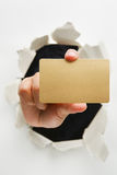 Hand breakthrough wall holding empty golden card. One of the breakthrough series stock photography