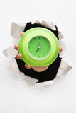 Hand breakthrough wall holding green clock. One of the breakthrough series stock photography