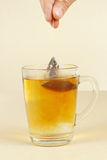 Hand brews tea bag in glass of hot water Royalty Free Stock Images