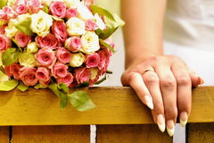 Hand of the bride with a bouquet near. Bride's hand with a wedding ring next to a bouquet of flowers Royalty Free Stock Photo