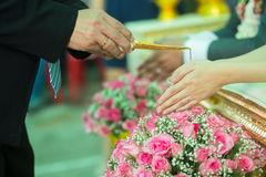 Hand of a bride and groom receiving holy water. From elders in Thai culture wedding ceremony Stock Photography