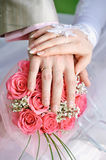 Hand the bride and groom with the rings lying on the bridal bouquet Royalty Free Stock Photos