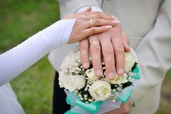 Hand the bride and groom with rings on wedding bouquet Royalty Free Stock Image