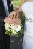 Hand the bride and groom with rings on wedding bouquet Royalty Free Stock Photo