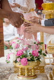 Hand of a bride receiving holy water from elders in thai culture wedding ceremony Royalty Free Stock Photography