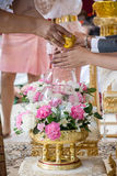 Hand of a bride receiving holy water from elders in thai culture wedding ceremony. Thai culture Stock Photos