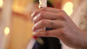 Hand of bride with ring and candle in church. Closeup hand of bride with golden wedding ring and candle in church during wedding ceremony on first plan. Soft stock video