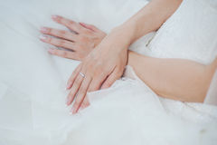 Hand of bride with wedding ring. White gold ring with diamonds on the hand of the bride. Bride in white dress Stock Images