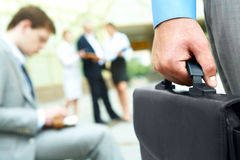 Hand with briefcase. Close-up of businessman hand holding briefcase in working environment royalty free stock photography