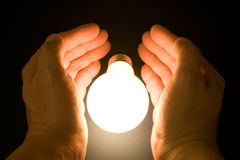 Hand and a Bright Light Bulb Royalty Free Stock Photos