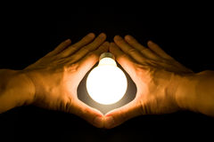 Hand and a Bright Light Bulb Royalty Free Stock Images