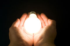 Hand and a Bright Light Bulb Stock Photos