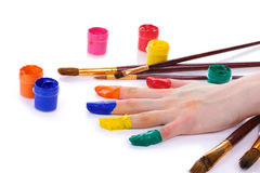 Hand in bright paint and brushes Royalty Free Stock Photo