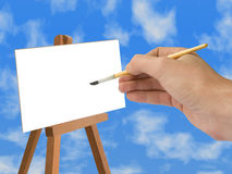 Hand with brush. White paper on easel Royalty Free Stock Photos