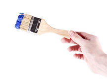 Hand with brush and blue paint isolated Stock Images