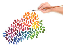 Hand with brush and color painted background Stock Images