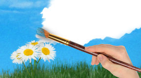 The hand with a brush draws a landscape. The blue sky and camomiles in the field Stock Images