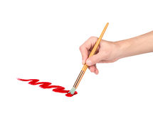 Hand with a brush draws red line Stock Image