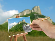 Hand with brush, mountain scene. On paper Royalty Free Stock Images