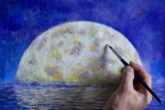Hand with brush paint a orange big moon in blue, reflection of moon in ocean, sea, water. Royalty Free Stock Photo