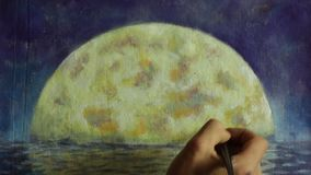 Hand with brush paint a orange big moon in blue, reflection of moon in ocean, sea, water. stock video footage
