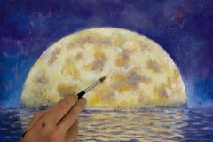 Hand with brush paint a orange big moon in blue, reflection of moon in ocean, sea, water. Stock Photography