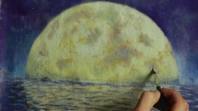 Hand with brush paint a orange big moon in blue, reflection of moon in ocean, sea, water. stock video