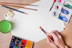 Hand with brush painting. With watercolor and blank white paper sheet Stock Images