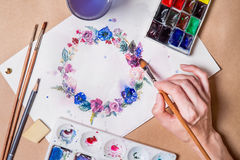 Hand with brush painting. Hand with brush painting with watercolors round wreath of flowers Stock Photography