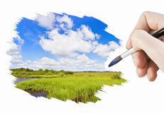 Hand with a brush paints a landscape Royalty Free Stock Photo