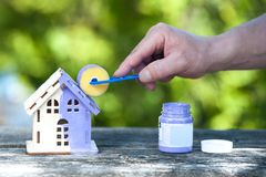 Hand with brush paints a toy house in lavender color, the background is a green garden. Housing construction, building, painting, home improvement, home royalty free stock photo