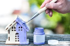 Hand with brush paints a toy house in lavender color, the background is a green garden. Housing construction, building, painting, home improvement, home royalty free stock photos