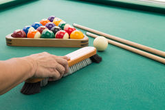 Hand brushing snooker pool billards table with balls and cue. Hand brushing surface of green snooker pool billards table with balls and cue Royalty Free Stock Photography