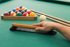 Hand brushing snooker pool billards table with balls and cue. Hand brushing surface of green snooker pool billards table with balls and cue Stock Images
